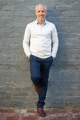 Buy stock photo Portrait of a mature businessman standing with his hands in his pockets against a brick wall