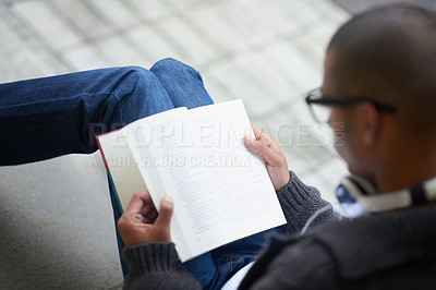 Buy stock photo Cropped shot of a college student reading a book while sitting outside at campus