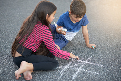 Buy stock photo Shot of a cute little boy playing tic tac toe with his sister on the pavement outside their house