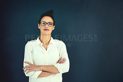 Buy stock photo Portrait of a confident young businesswoman standing with her arms folded in the studio