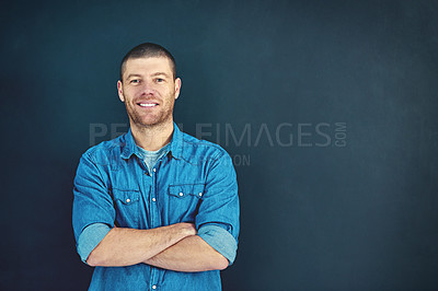 Buy stock photo Portrait of a confident young businessman standing with his arms folded in the studio