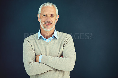 Buy stock photo Portrait of a mature businessman standing with his arms folded in the studio