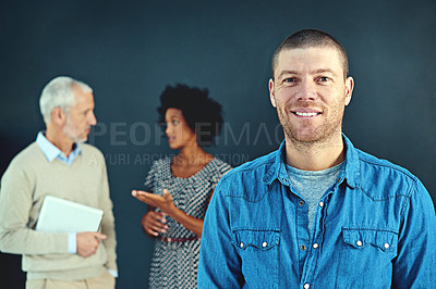 Buy stock photo Studio portrait of a young businessman posing with his colleagues in the background