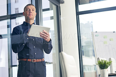 Buy stock photo Shot of a thoughtful businessman using a digital tablet in a modern office