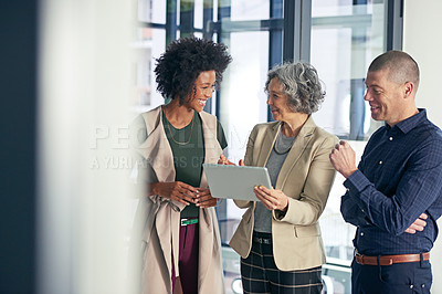 Buy stock photo Shot of a team of colleagues using a digital tablet during an informal meeting
