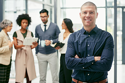 Buy stock photo Portrait of a businessman standing in an office with his colleagues in the background