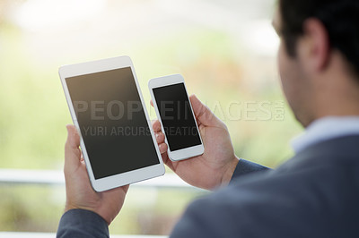 Buy stock photo Cropped shot of corporate businessmen looking at a digital tablet and a cellphone in his hands