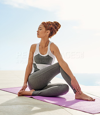 Buy stock photo Shot of a young woman practicing yoga by herself outside