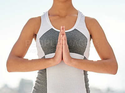 Buy stock photo Shot of an unidentifiable young woman standing with her hands together in a yoga pose outside