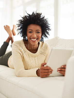 Buy stock photo Portrait of an attractive young using her tablet while lying on the sofa at home