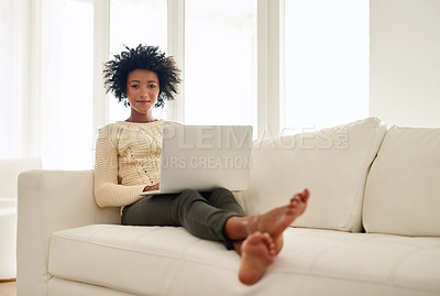 Buy stock photo Portrait of an attractive young using her laptop while sitting on the sofa at home