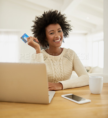 Buy stock photo Portrait of an attractive young woman shopping online using her laptop while sitting on the sofa at home