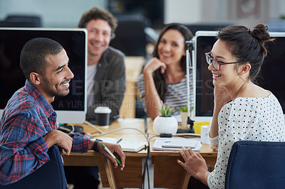 Buy stock photo Shot of a group of smiling designers sitting at their workstations in an office
