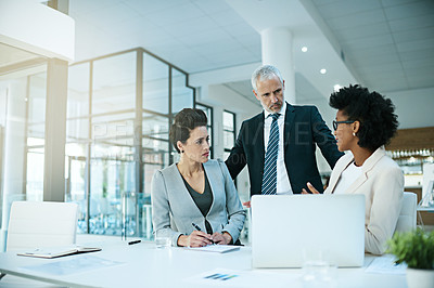 Buy stock photo Shot of a group of businesspeople using a laptop while having a meeting in the boardroom