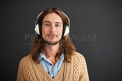 Buy stock photo Studio portrait of a young man listening to music on headphones against a gray background