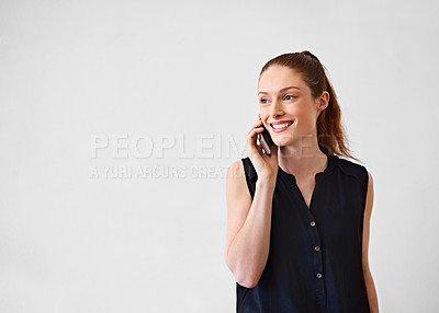 Buy stock photo Studio shot of a young woman talking on a cellphone against a gray background