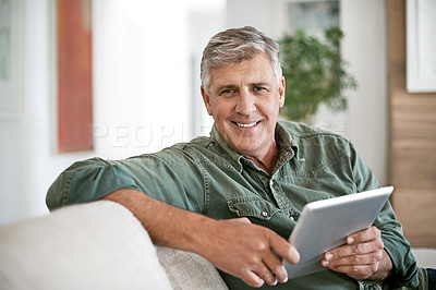 Buy stock photo Portrait of a mature man using a digital tablet at home