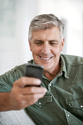 Buy stock photo Cropped shot of a mature man texting on a cellphone at home