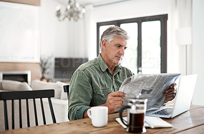 Buy stock photo Cropped shot of a mature man reading a newspaper while working on his laptop at home