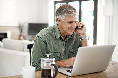 Buy stock photo Cropped shot of a mature man talking on a cellphone while working on his laptop at home