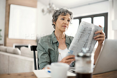 Buy stock photo Shot of a mature woman reading the newspaper while working on her laptop at home