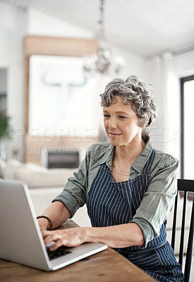 Buy stock photo Shot of a mature woman working on her laptop at home