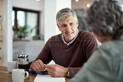 Buy stock photo Shot of a mature man having a conversation with his wife blurred out in the foreground