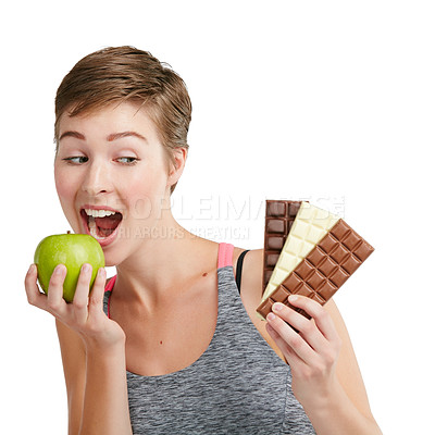 Buy stock photo Studio shot of a fit young woman deciding whether to eat chocolate or an apple against a white background