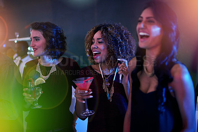 Buy stock photo Shot of a group of friends enjoying themselves at a nightclub