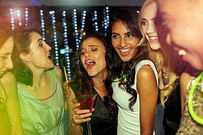 Buy stock photo Shot of a group of young people enjoying themselves at a nightclub