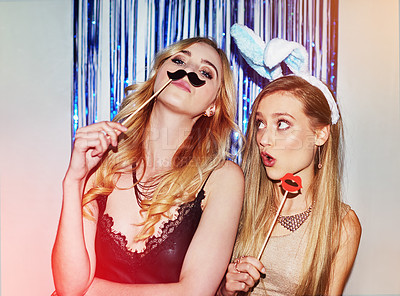 Buy stock photo Shot of two beautiful young women having fun with props in a photobooth