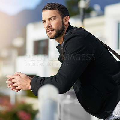 Buy stock photo Shot of a thoughtful young man leaning against a railing outside