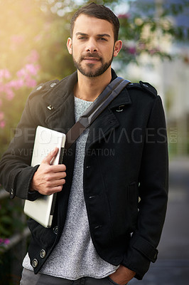 Buy stock photo Shot of a handsome young man standing outdoors and holding a laptop