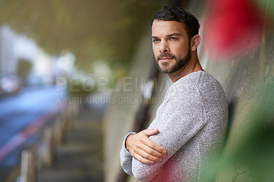 Buy stock photo Shot of a handsome young man out in the city