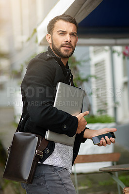 Buy stock photo Shot of a handsome young man carrying his phone and laptop while out in the city
