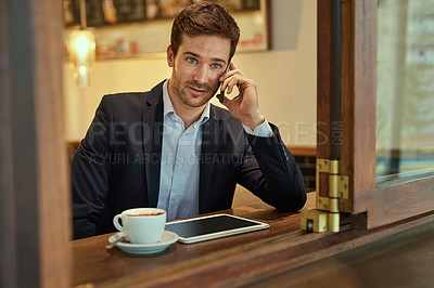 Buy stock photo Shot of a young businessman making a phonecall while sitting in a coffee shop