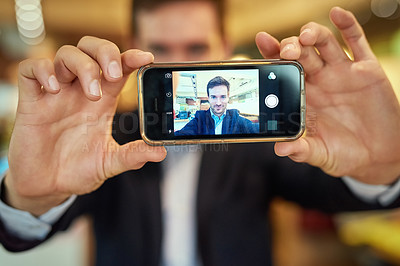 Buy stock photo Shot of a young businessman taking a selfie while sitting in a coffee shop