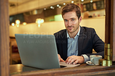 Buy stock photo Portrait of a young businessman using his laptop while sitting in a coffee shop