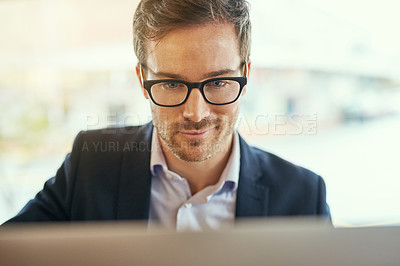 Buy stock photo Shot of a young businessman using his laptop while sitting in a coffee shop