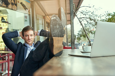 Buy stock photo Portrait of a young businessman looking relaxed while sitting in a coffee shop