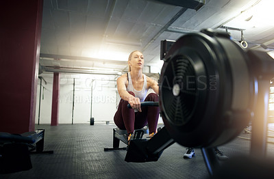 Buy stock photo Shot of a young woman working out with a rowing machine at a gym