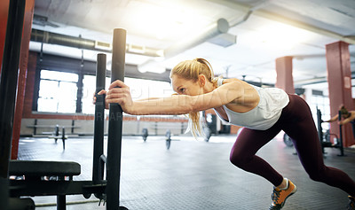 Buy stock photo Shot of a young woman working out with a weighted sled at a gym