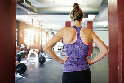 Buy stock photo Rearview shot of a woman standing with her hands on her hips at a gym