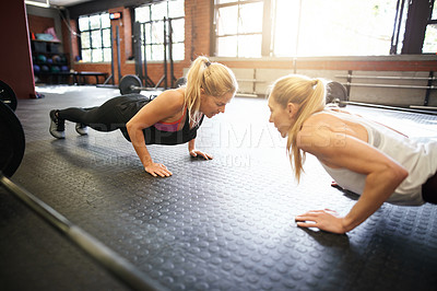 Buy stock photo Shot of two young women doing pushups opposite each other at a gym