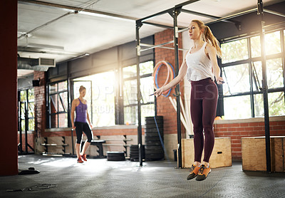 Buy stock photo Shot of a young woman skipping with a jumprope at a gym