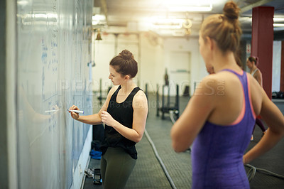 Buy stock photo Shot of two young women writing notes on a board at a gym
