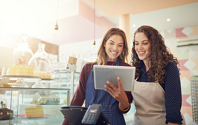 Buy stock photo Shot of a young woman showing her colleague something on her tablet while they stand in their cake shop