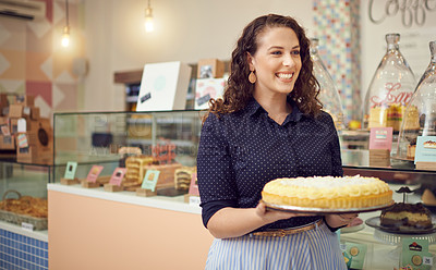 Buy stock photo Shot of a young woman carrying a large cake in her bakery