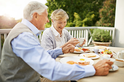 Buy stock photo Shot of a senior couple having breakfast on their balcony at home