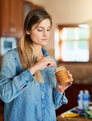 Buy stock photo Cropped shot of a young woman eating peanut butter out of the jar with a spoon